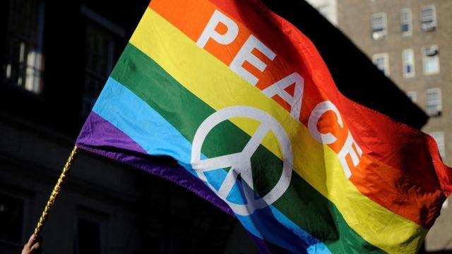 Bandeira colorida com paz escrito em inglês