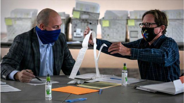 Funcionarios electorales revisando votos.