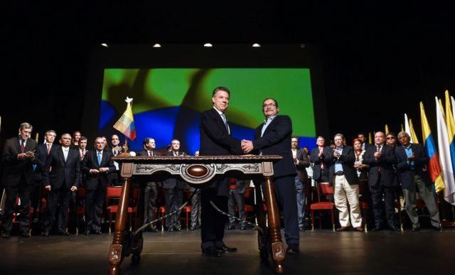 Juan Manuel Santos e líder das Farc, Timochenko, ao firmar acordo em 2016;