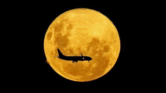 Un avión pasa por delante de la Luna, desde Curitiba, Brasil, el 9 de marzo de 2020.