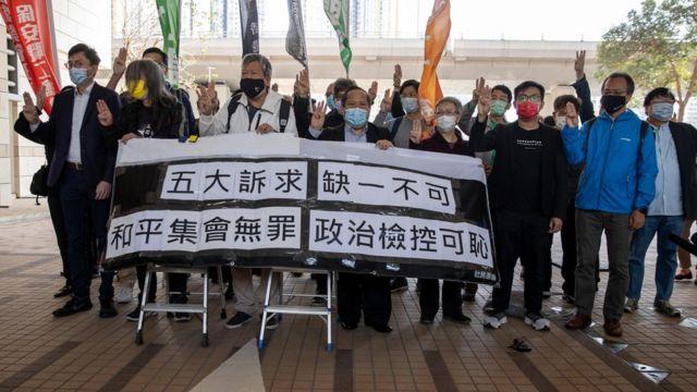 """香港""""反送中8·18未经批准集结""""案被告人进入西九龙法院大楼应讯前展示抗议标语(16/2/2021)"""