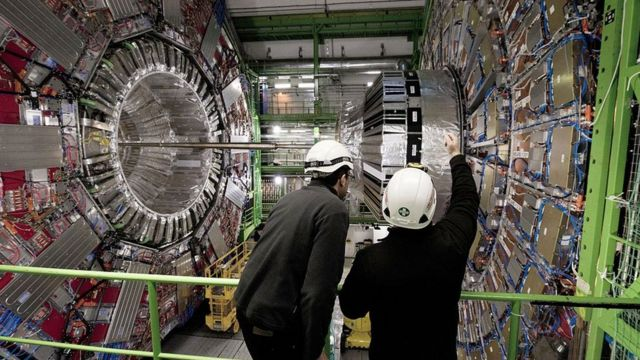 Dos personas observando el Gran Colisionador de Hadrones.