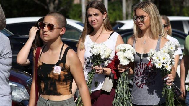 25日午後、銃規制を訴える活動をするエマ・ゴンザレスさん(写真左)など高校の生徒たちが登校した