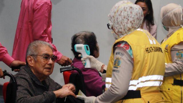 Petugas Kesehatan Karantina Bandara Soekarno Hatta melakukan pemeriksaan acak suhu badan penumpang yang baru mendarat di Terminal 3 Bandara Soekarno Hatta, Tangerang, Banten, Rabu (22/01).