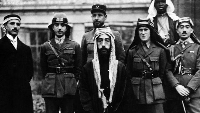 الأمير فيصل، الذي صار بعد ذلك ملك العراق، مع أفراد حاشيته في مؤتمر باريس للسلام عام 1919 ويظهر على يمينه العقيد لورانس بغطاء الرأس العربي، كما يظهر نوري السعيد (الثاني من يسار الصورة) الذي صار رئيسا للوزراء فيما بعد