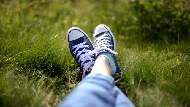 Piernas estiradas sobre el pasto.