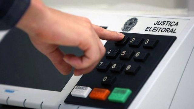 Pessoa digitando números em urna eletrônica