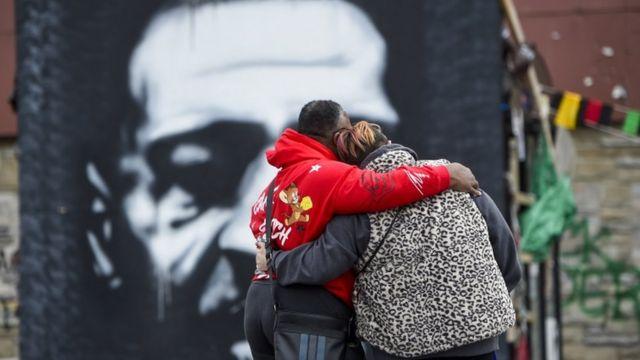Duas pessoas de costas para a foto e abraçadas, em frente a grafite de George Floyd pintado