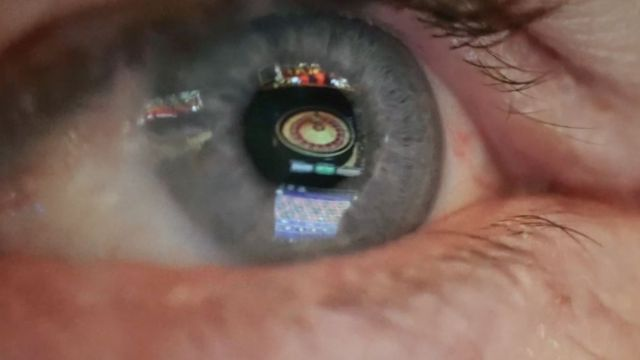 an eye reflecting a roulette wheel