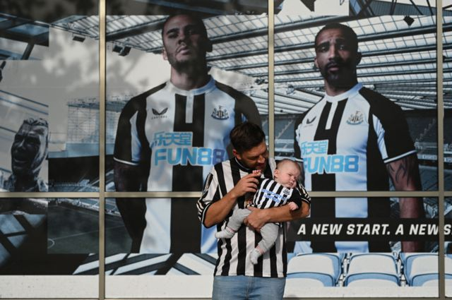 Newcastle United supporter Ryan Arrowsmith poses with three-month old son Lewis outside the club shop at St James' Park in Newcastle upon Tyne in northeast England on October 8, 2021, after the sale of the football club to a Saudi-led consortium was confirmed the previous day.