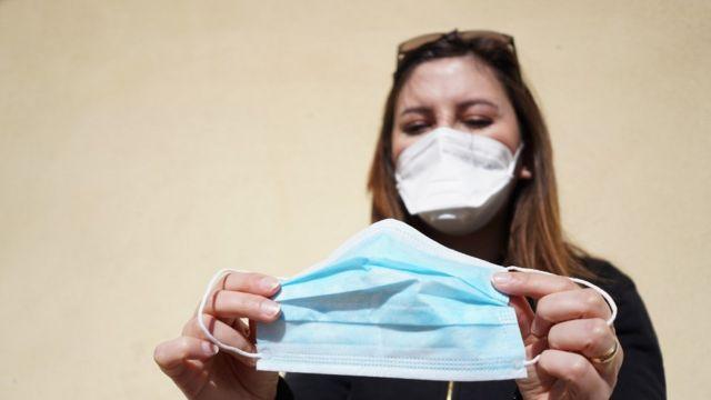Uma mulher com uma máscara no rosto segurando outra máscara