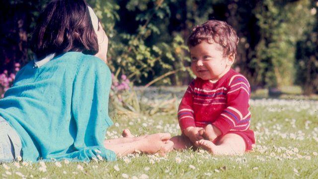 Fotografia tirada por Vladimir Herzog em Regent Park, Londres, junho de 1967. Clarice Herzog, deitada sobre os cotovelos e de costas para a câmera, olha para Ivo Herzog bebê sentado à sua frente, que a olha de volta.