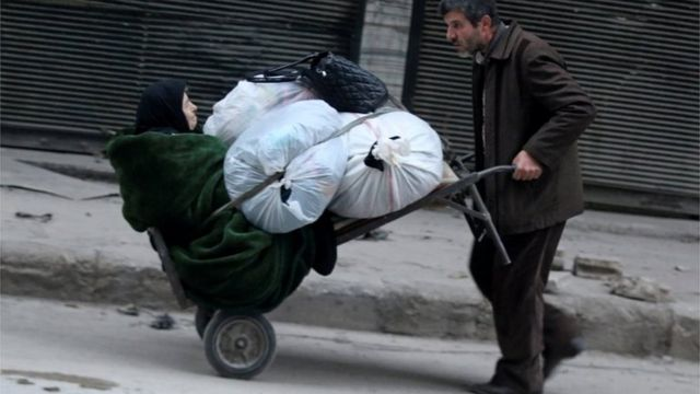 A man pushes a cart carrying an elderly woman and belongings as they flee deeper into the remaining rebel-held areas of Aleppo, Syria December 12, 2016