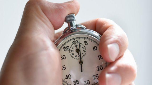 Una mano sostiene un reloj.