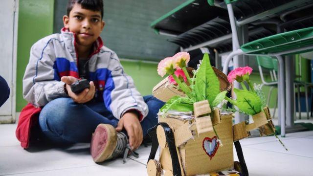 Guilherme e seu Wall-E de papelão, que se move por controle remoto e tem coração que brilha