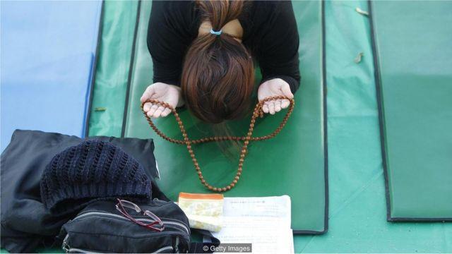 Mãe reza por filhos durante preparação de exame na Coreia do Sul