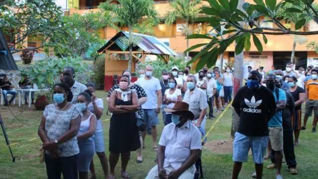Les électeurs font la queue au bureau de vote de Beau Vallo, sur l'île de Mahé, le 24 octobre 2020 pendant les élections présidentielles et législatives