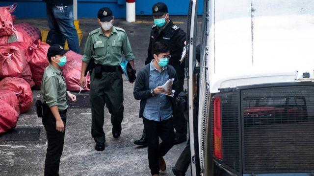 前香港立法会议员区诺轩(图中蓝色上衣者)在九龙荔枝角收押所被押上囚车(2/3/2021)