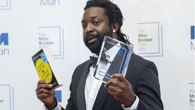 Escritor Marlon James muestra su libro y el premio que consiguió.