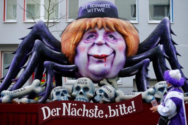"""Lutka sa karnevala u Diseldorfu iz gebruara 2018. prikazuje nemačku kancelarku Angelu Merkel kao crnu udovicu.. Na transparentu piše: """"Sledeći, molim!"""""""