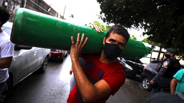 Um homem carrega um cilindro de oxigênio enquanto pessoas fazem fila para comprá-lo de vendedores particulares para tratar de parentes doentes em Manaus, 15 de janeiro de 2021