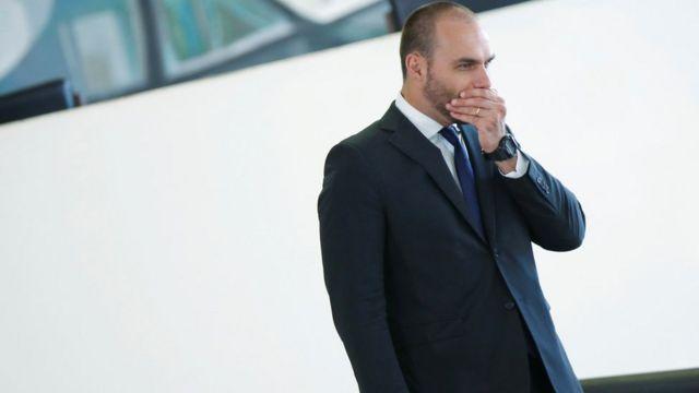 Eduardo Bolsonaro aparece de perfil caminhando em corredor e tapando a boca com a mão
