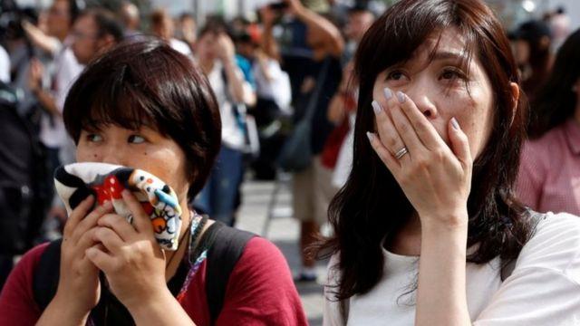 Японки наблюдают за обращением императора к нации
