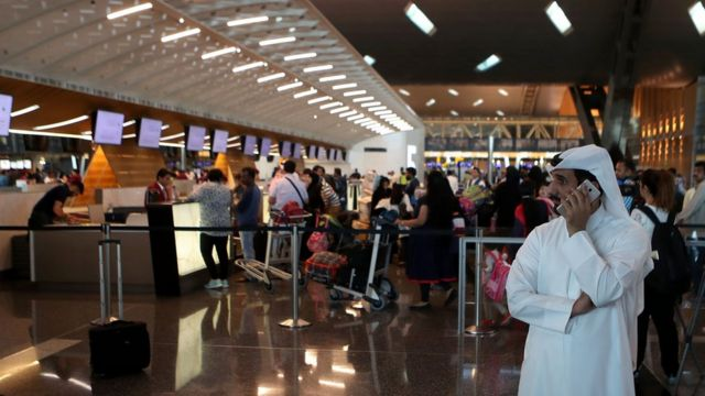 Passengers wait to check-in at a Qatar Airways counter in the Hamad International Airport in the Qatari capital Doha on June 12, 2017