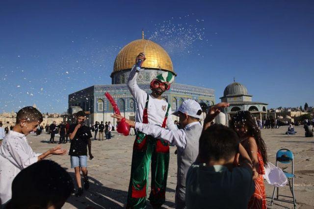 أطفال يتحلقون حول بائع بالونات في ساحة المسجد الأقصى صباح الخميس
