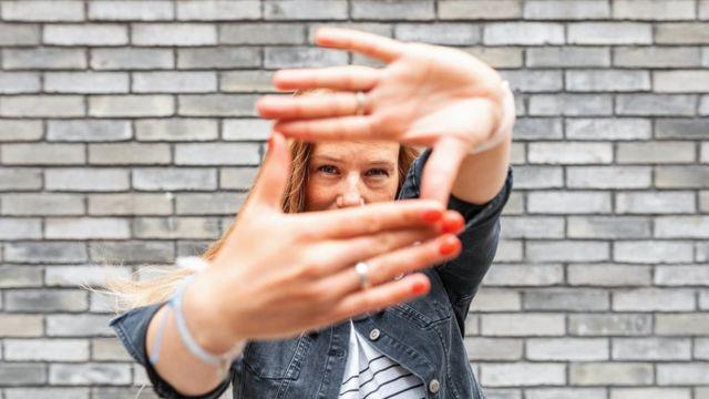 Parmak çerçevesi işareti yapan gri tuğla duvara karşı kadının yakın çekimi