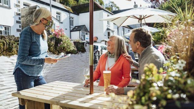 一对夫妇在啤酒花园里点饮料(资料照片)