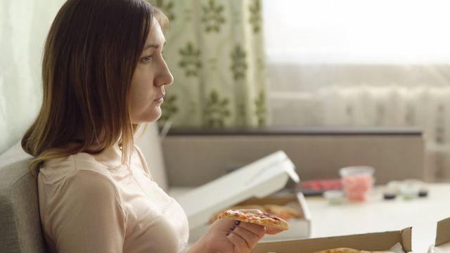 Mujer triste comiendo pizza sola en un sofá