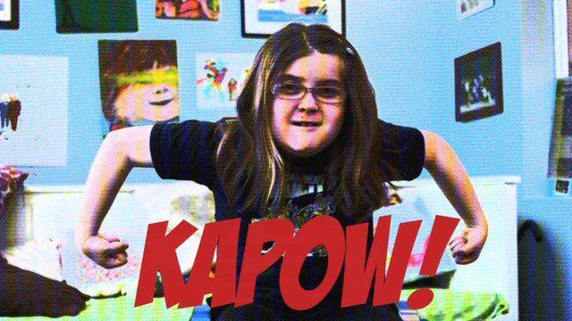 Emily White in superhero pose with KAPOW written across the middle