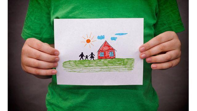 Criança segura um desenho de casa e família