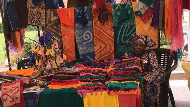 Une femme, assise derrière son étal, vend des vêtements en batik.