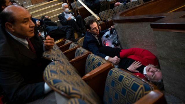O deputado Jason Crow (centro), que anteriormente serviu no Exército dos EUA, conforta a deputada Susan Wild quando os apoiadores de Trump invadiram a sede do Congresso.