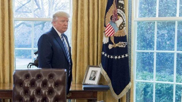 Donald Trump con un retrato de su padre en el Casa Blanca.