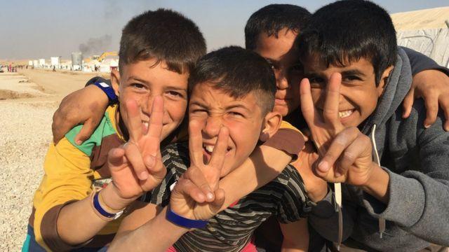 أطفال نازحون عراقيون يرفعون إشارة السلام