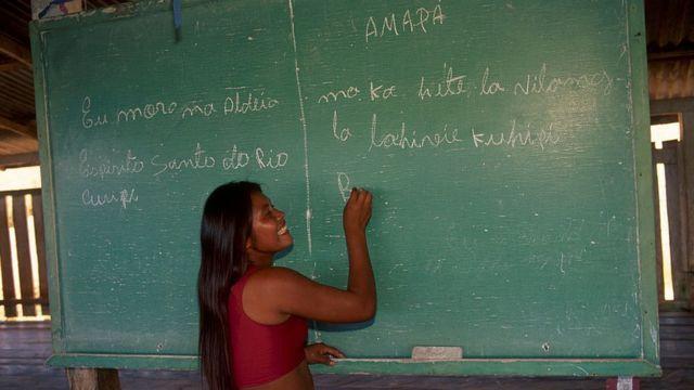 Una mujer indígena escribe sobre una pizarra en Brasil.