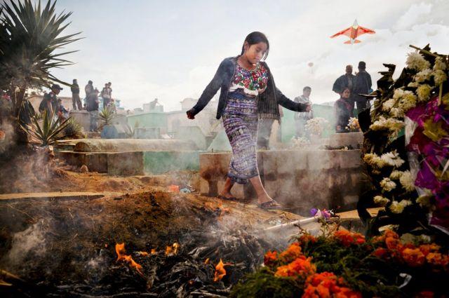 A young woman walks between tombstones.