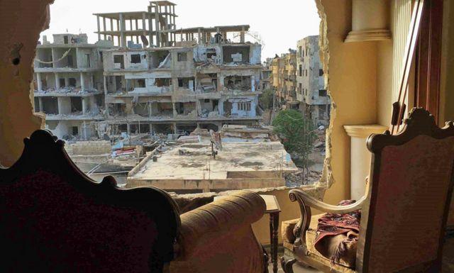 Sillas al frente de una pared destruida y de un edificio bombardeado.