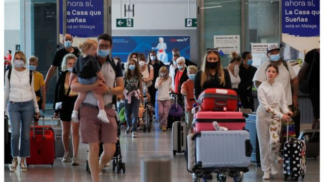 British tourists wearing protective face masks walk with their luggage, as they arrive at Malaga-Costa del Sol Airport for sightseeing, amid the coronavirus disease (COVID-19) outbreak in Malaga, Spain, July 19, 2021. REUTERS/Jon Nazca