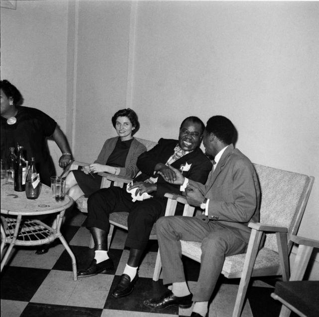 Le musicien de jazz américain Louis Armstrong (au milieu), tout souriant, serre la main d'un autre homme.