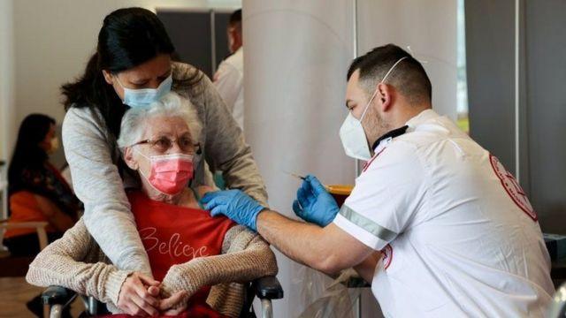 امرأة مسنة تحصل على اللقاح