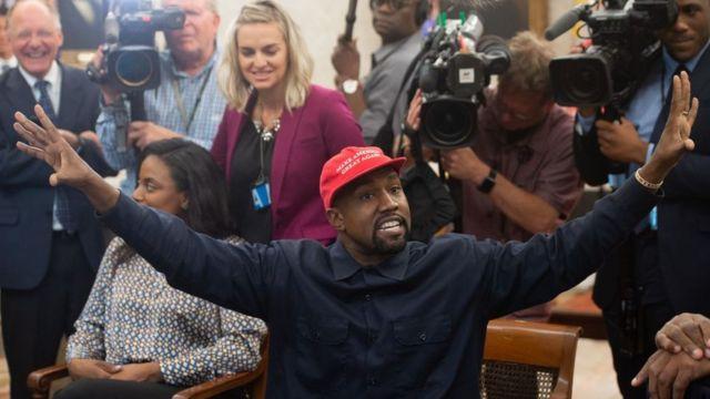 Kanye West con una gorra de Make America Great Again y rodeado de periodistas.