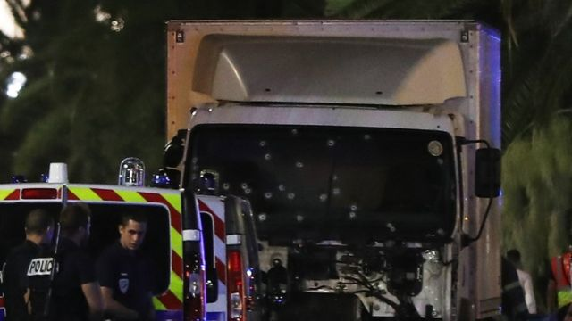 Lorry, showing its windscreen full of bullet holes, with a police van and police officers in front