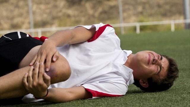 Niño tirado en el campo con dolor en la rodilla.