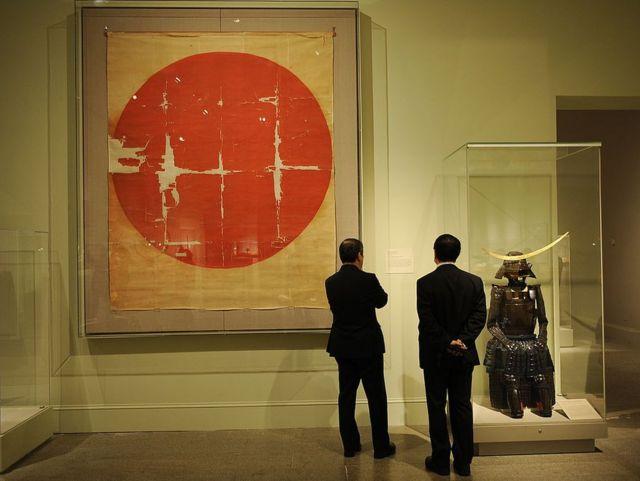 """Bandeira histórica japonesa do siglo XVI ao lado de um samurai da armadura na exibição """"A arte do samurai: armas e armaduras japonesas, 1156-1868"""" em 2009 no Metropolitan Museum of Art de Nueva York."""