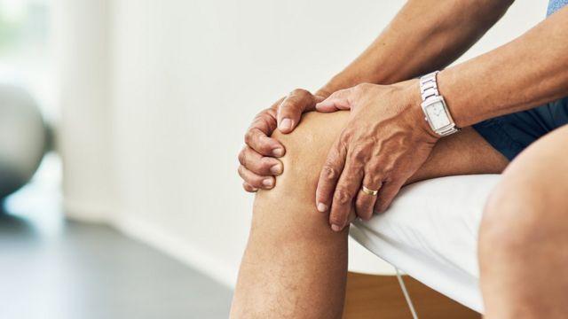 Hombre tocándose la rodilla