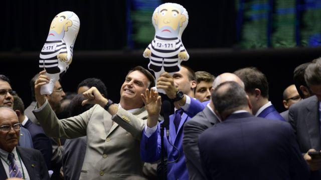 Jair Bolsonaro e Eduardo Bolsonaro com bonecos representando Lula preso, em 2016, no plenário da Câmara